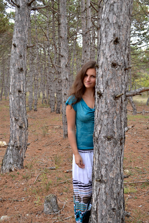 crepuscle: The young brown-eyed girl the brown-haired woman in a dress in the coniferous wood