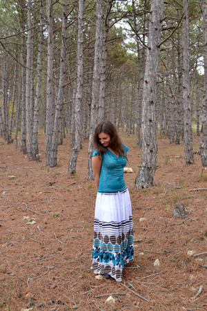 The young brown-eyed girl the brown-haired woman in a dress in the coniferous wood