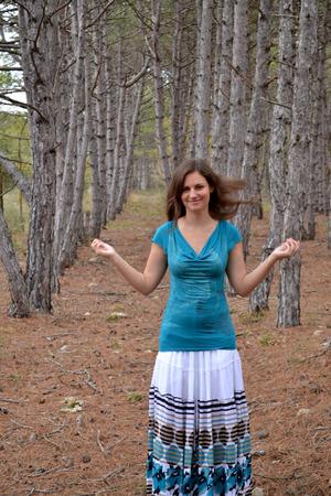 De jonge bruin-eyed meisje de bruinharige vrouw in een jurk in het naaldhout Stockfoto