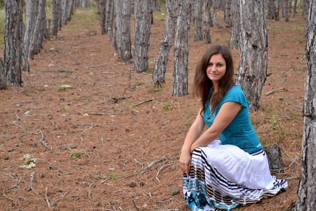 teener: The young brown-eyed girl the brown-haired woman in a dress in the coniferous wood
