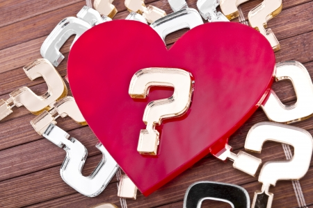 plexiglas: Red plexiglas heart with a gold question mark on it  lies on a wooden background with many other question marks  Stock Photo