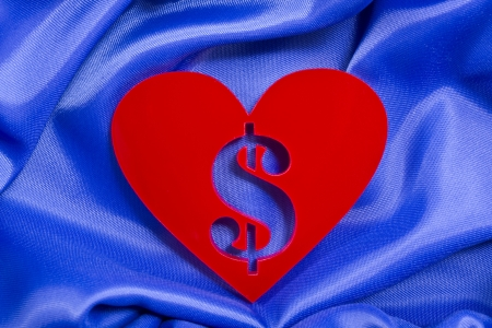 plexiglas: Red heart shape with dollar sign inside of a plexiglas material on a blue silk background  Stock Photo