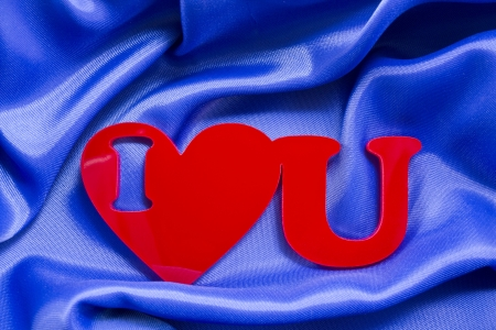 plexiglas: I love you red shape of a plexiglas material on a blue silk background. Stock Photo