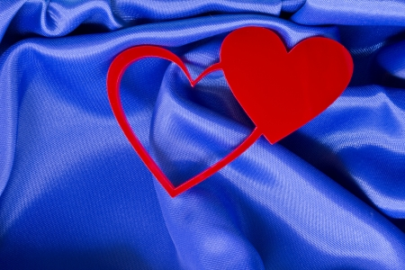 plexiglas: Two red hearts on a blue silk background.