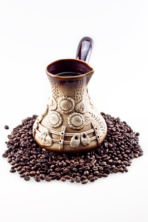 grains of coffee: Hecho a mano olla de caf� con granos de caf� en el fondo aislado en blanco