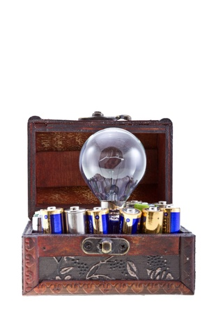 Batteries energy for an idea concept shot. Opened treasure chest with batteries and and a bulb lamp inside isolated on white.  photo