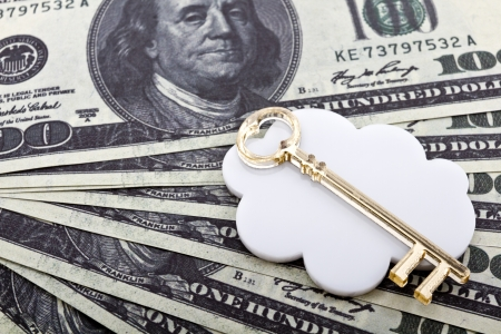 Golden key shape made of  lie on a white cloud shape against a dollar currency background  photo