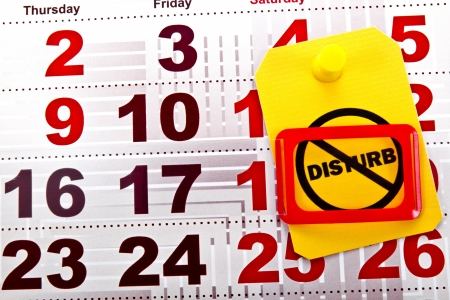Do not disturb at weekend concept shot. Do not disturb yellow label/tag on a paper calendar background. Stock Photo - 20102011