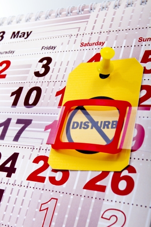 Do not disturb at weekend concept shot. Do not disturb yellow label/tag on a paper calendar background. Stock Photo - 20102001