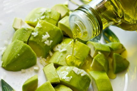 green salad: Pouring olive oil over salad