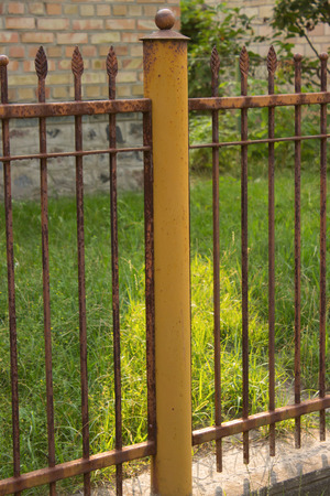 rusty fence: yellow pole and a rusty fence with the top in the form of forged leaves, on a background of grass and brick, Sunny day