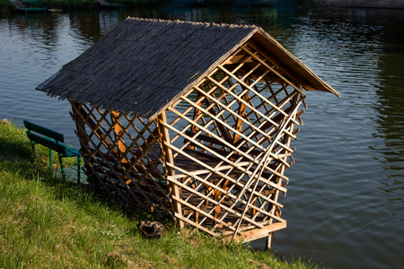 roofed house: roofed house on the waterfront, roof covered with bamboo,on a Sunny day Stock Photo