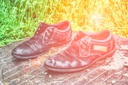 Old mens shoes. Abandoned on the street after a rain. Worn and Stock Photo
