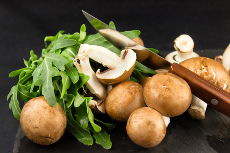 Fresh raw mushrooms brown champignons and green arugula on a dar