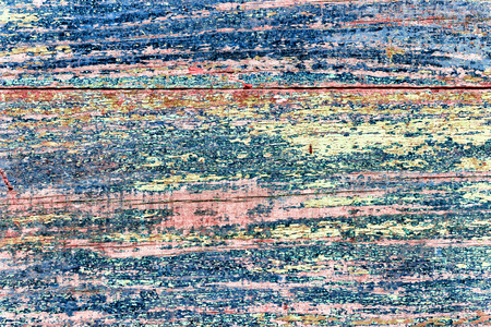 wood background blue green pink colored crackled paint.