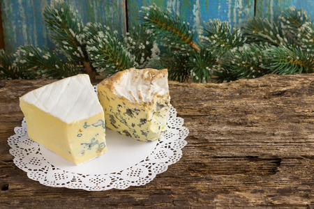 Cambozola, Bleu dauvergne noble gourmet cheeses with blue and white mold on wooden background with branches of pine needles Christmas card. Copy space