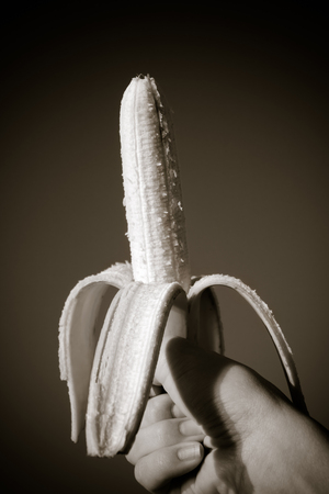 Female hand with red nails holding a banana.A hand holds a peeled banana on a black background. Tropical Fruit Banana peel Toning sepia Stock Photo