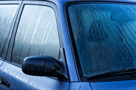 Fogged part of the car, windshield, part of the front door and mirrors. Morning condensate on a car.