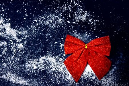 Red festive decorative bow on dark blue background. Blank for writing Christmas or new year baking recipes. Copy space. Stok Fotoğraf