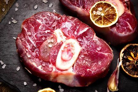 Raw ossobuco meat, beef steak with spices and salt for cooking, black stone concrete background, a traditional dish of Italian cuisine, which is a veal shank.