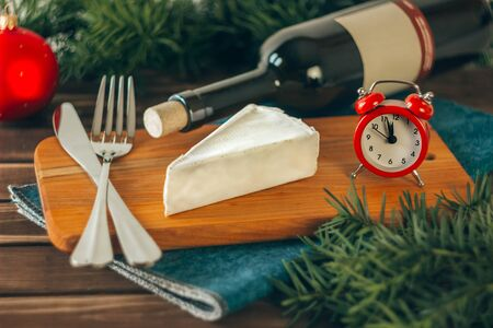 Brie cheese, a bottle of wine, coniferous green branches, a red alarm clock, and Cutlery on a wooden background. Goodies for the holiday. The concept of Christmas and the New year. Toned