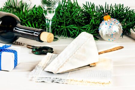Brie cheese, bottle of wine, glass, corkscrew, coniferous green branches, gift box tied with a blue ribbon, holiday decorations on a wooden background. Goodies for the holiday. The concept of Christmas and New year background. Toned