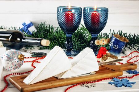 Brie cheese, bottle of wine, glass, corkscrew, coniferous green branches, gift box tied with blue ribbon, symbol of the year 2020 candle in the form of a mouse on a wooden background. Goodies for the holiday. The concept of Christmas and New year background. Toned Stock Photo