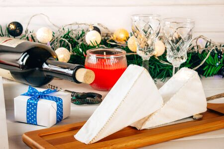 Brie cheese, a bottle of wine, coniferous green branches on a wooden background. Goodies for the holiday. The concept of Christmas and the New year. Toned Stock Photo