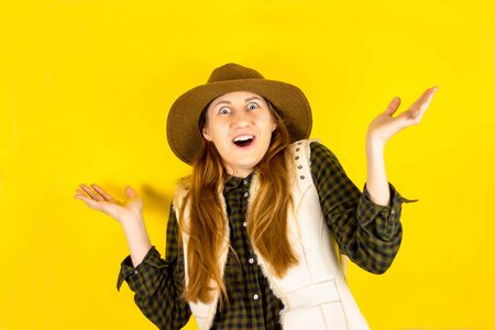 Portrait of a happy brown-haired girl makes a gesture with her fingers, shows an empty space with a surprised expression on her face, expresses surprise, looks with a charming smile, wears a hat on her head and a shirt, and a white vest. Yellow background. Concept of peoples emotions.