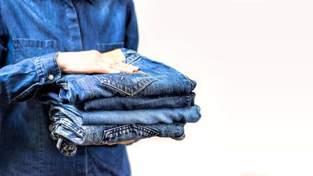 A woman's hand holds a stack of clean folded ironed things made of blue cotton denim. Cleaning the closet. Love for denim things. Copy of the space