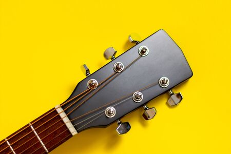 Part of the neck of an acoustic guitar and a string-tensioning bar. Close up. On yellow background. copy space. 写真素材