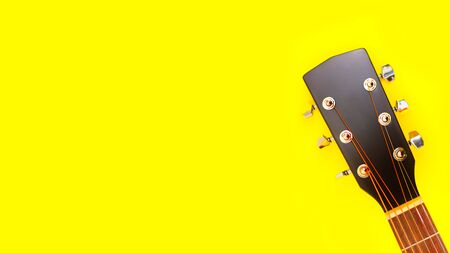 Part of the neck of an acoustic guitar and a string-tensioning bar. Close up. On yellow background. copy space. banner 写真素材