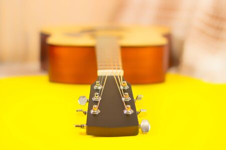 Part of the neck of an acoustic guitar and a string-tensioning bar. Close up. On yellow background. copy space. selective soft focus