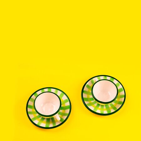 Beautiful little green striped two tea coffee cups and saucers on a yellow background. The concept of home tea drinking, comfort. Square