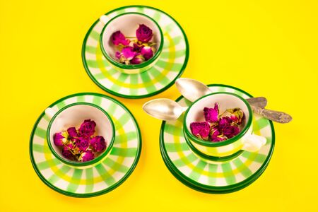 Beautiful little green striped two tea coffee cups and saucers spoons on a yellow background. The concept of home tea drinking, comfort. Banner.