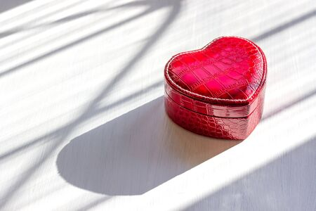 Red heart-shaped jewelry box made of leather on a white wooden background, natural sunlight, hard shadows. Gifts for lovers. Valentine's day. Copy space. The concept of love and luxury. Stock fotó
