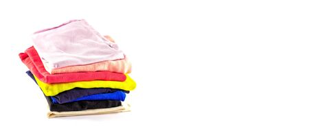 A stack of multicolored knitwear, t-shirts, stacked vertically, isolated on a white background. Fresh laundry. Banner. copy space Stock fotó