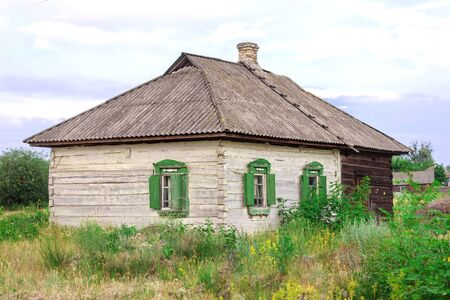 An old wooden rural abandoned house, white with green shutters and a gray roof