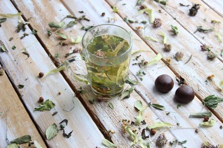 Glass with herbal tea on wooden background with dry herbs an chocolate sweets