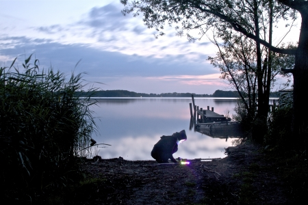 a women on a lake bank in the twilight
