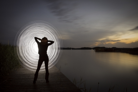 seem: a women in the sunset who play a light game Stock Photo