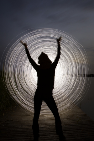 a women in the night who play a light game Stock Photo
