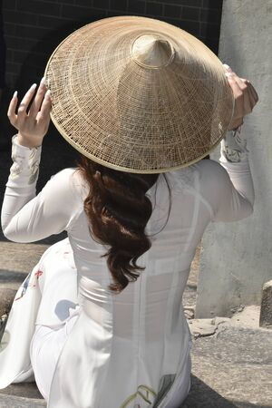 a lady in a white dress an a bamboo hat is sitting on a step