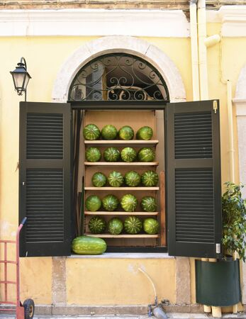 A merchant of fruits exposes the watermelons on selfs in a window