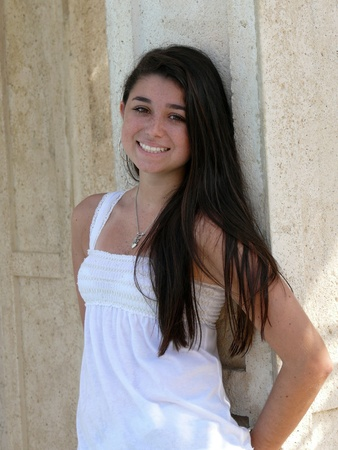 Attractive teenage girl with white dress and long brown hair.
