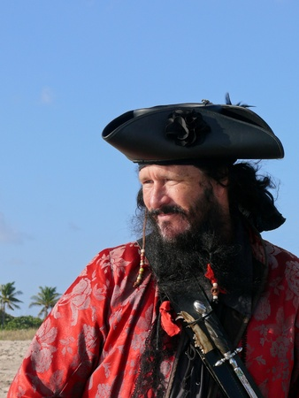 A half length portrait of a male pirate dressed in vintage clothes with weapons standing on the beach and looking out to sea. Stock Photo