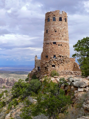 The weather stones of the watchtower form an historic replica of a prehistoric indian tower on the South Rim of the canyon and invite tourists to v isit on a sunny summer afternoon. photo