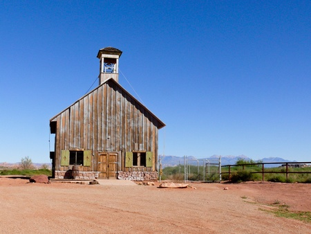 A vintage wooden schoolhouse with belltower standing in a fenced field in rural Arizona.