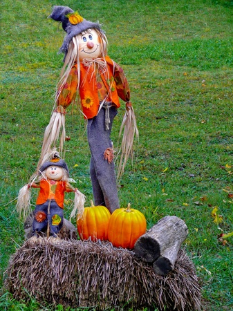 Straw scarecrows of a mother and her baby in colorful costumes standing next to a pile of straw, wood and pumpkins on an autumn day in the U.S. countryside