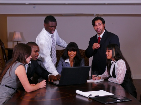 A group of three male and three female  young professionals discuss business in an office setting.